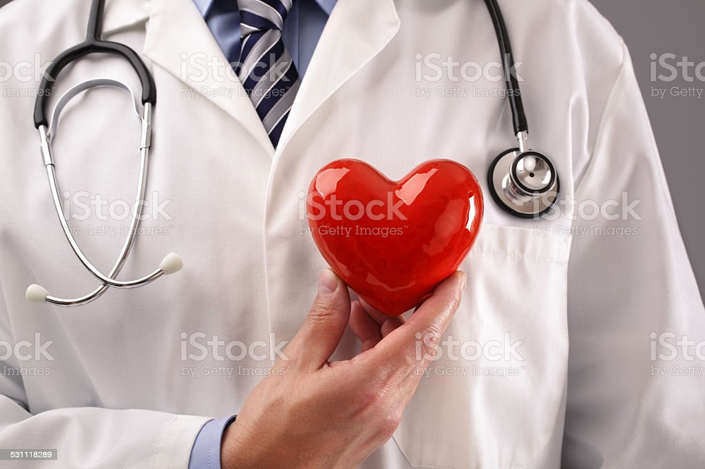 Doctor holding heart against chest stock photo