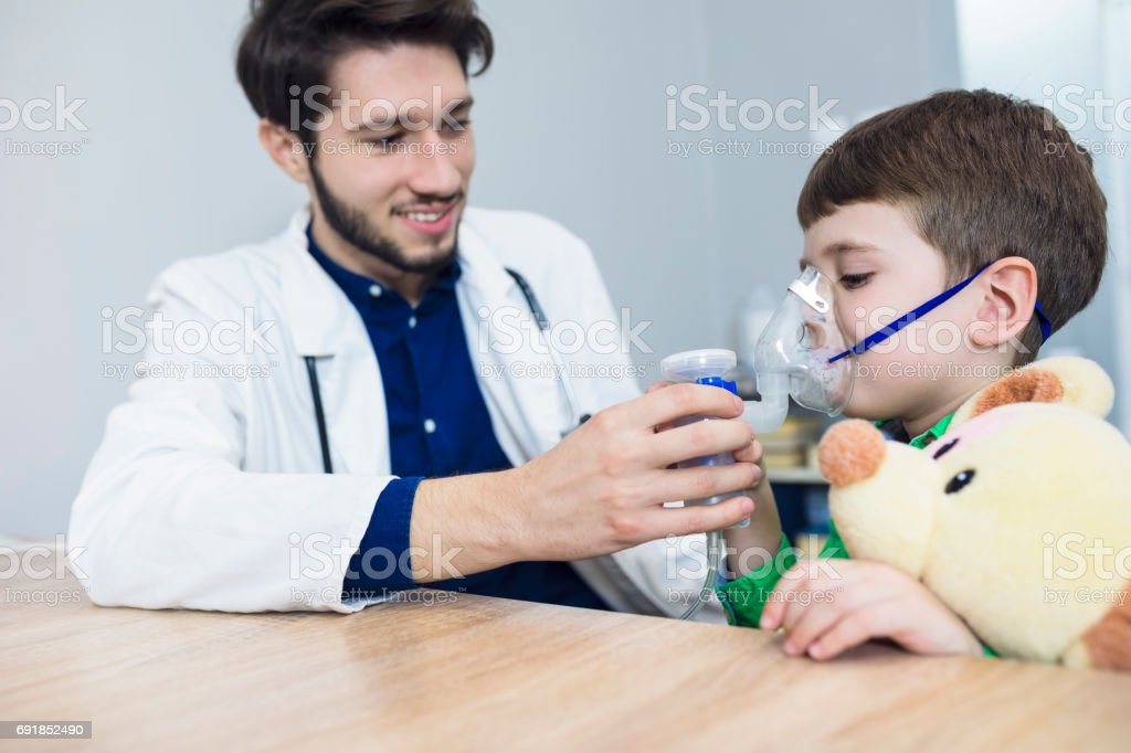 Doctor holding inhaler mask for kid breathing stock photo