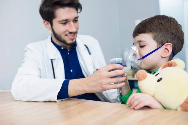 läkaren håller inhalatorn mask för barn som andas - andningssystem bildbanksfoton och bilder