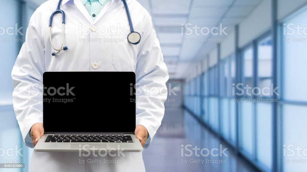Doctor holding laptop computer in front view stock photo