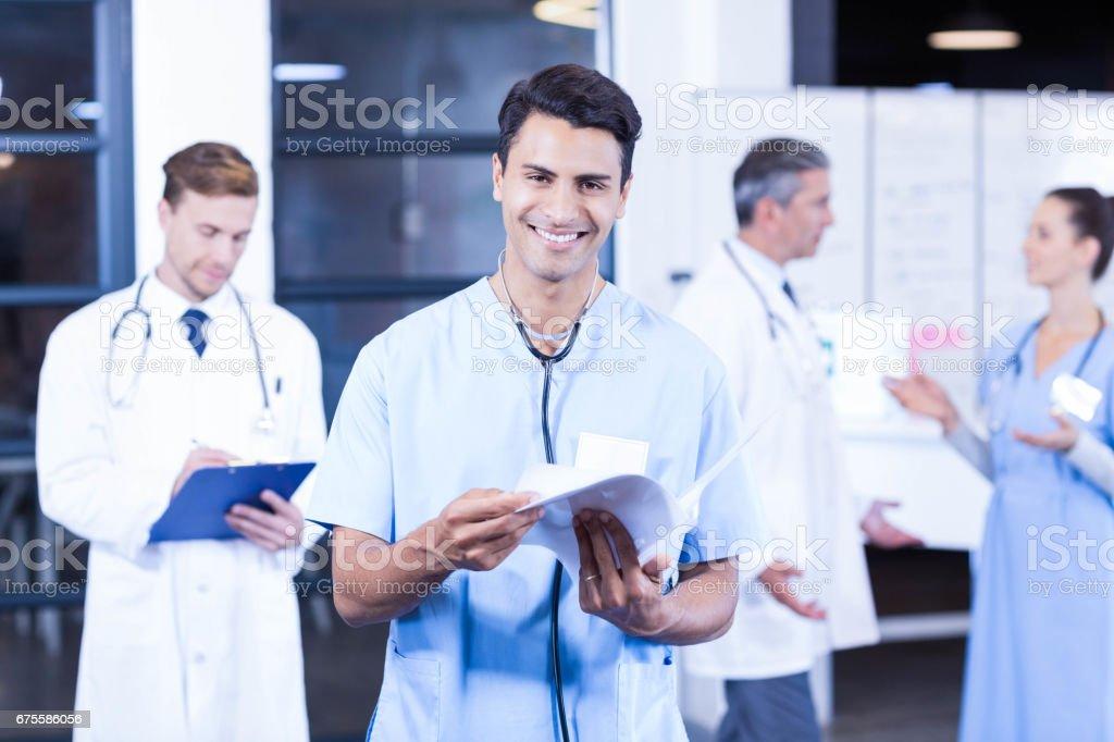 Médecin tenant rapport médical et souriant à la caméra photo libre de droits