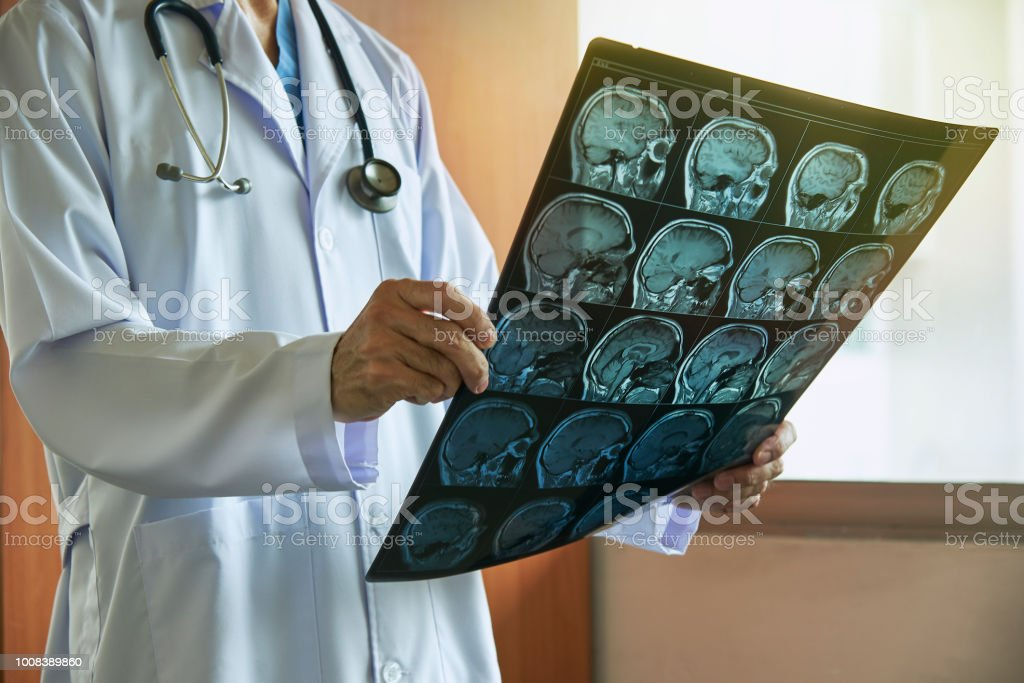 Doctor with stethoscope holding human brain MRI imaging in medical...