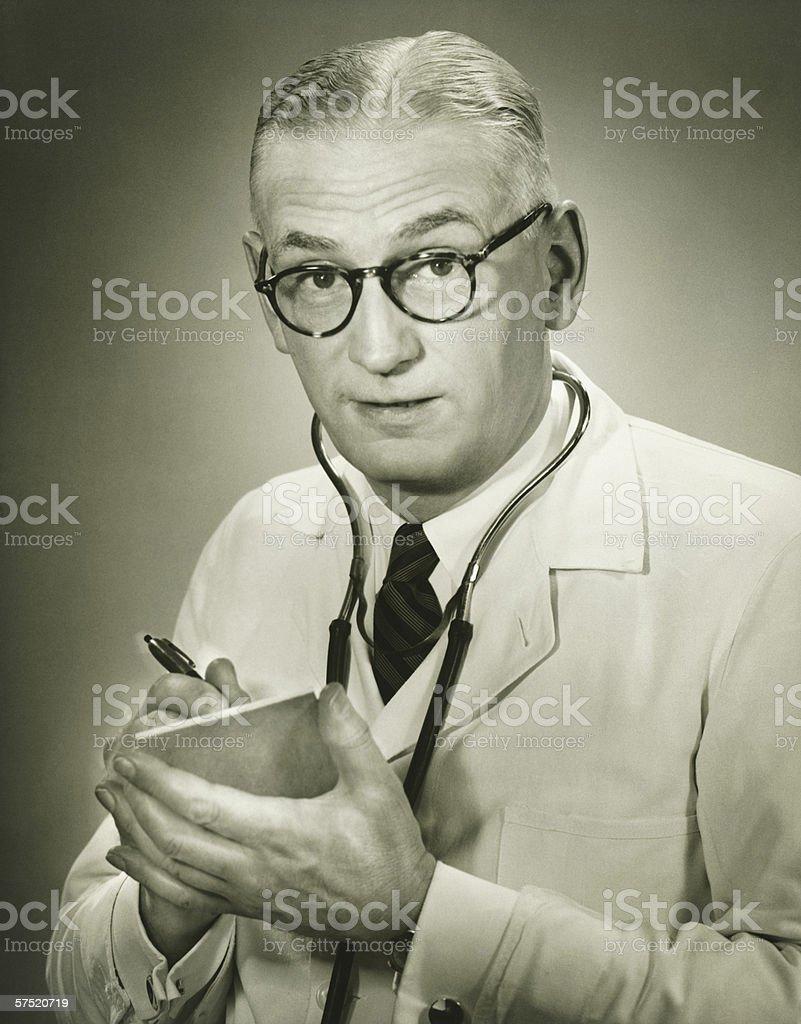 Doctor holding note pad posing in studio, (B&W), portrait stock photo