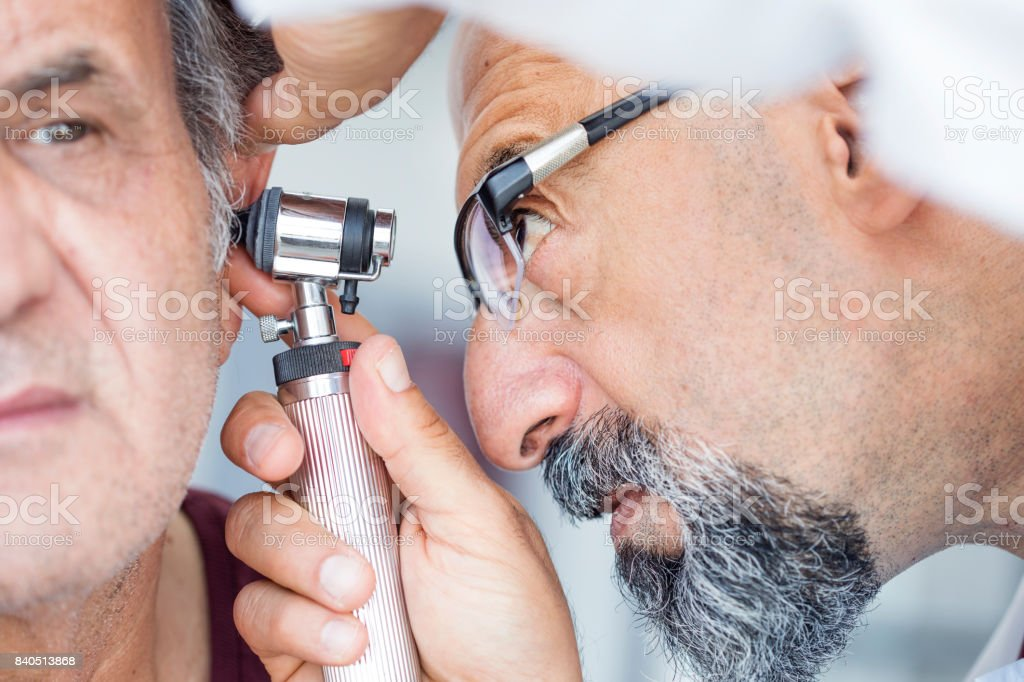 Doctor holding otoscope and examining ear of senior man stock photo