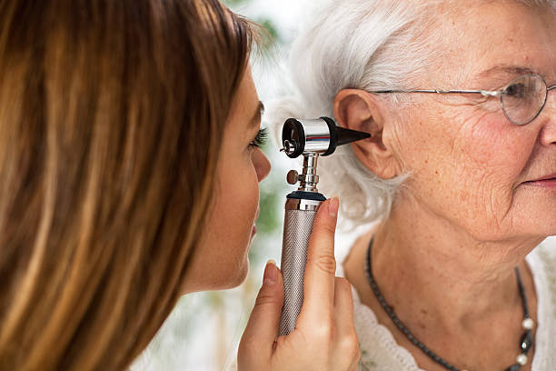 doctor holding otoscope and examining ear of senior woman - ear stock photos and pictures
