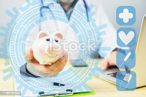 istock Doctor holding out your piggy bank wanting payment/ Your Savings To Pay Bill, insert coins to it,Stethoscope financial checkup or saving for medical insurance costs money plan fee Lifestyle concept 1138785352