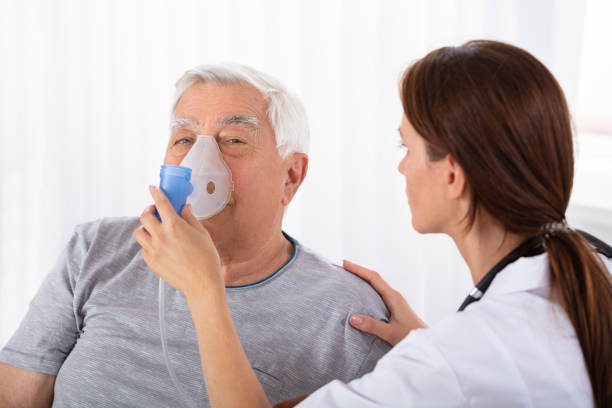 Doctor Holding Oxygen Mask Over Man's Face Young Female Doctor Holding Oxygen Mask Over Senior Male Patient's Face smoke inhalation stock pictures, royalty-free photos & images