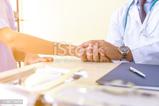 667827758 istock photo Doctor holding patients hand, encouraging his patient and telling her would be safe, recover an illness or cancer in doctors office at clinic or hospital with medical equipment foreground. 1190775529