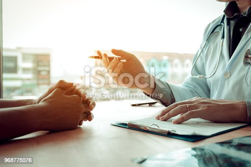 873418972istockphoto Doctor holding pen and talking serious to the patient about medication and treatment. 968775076