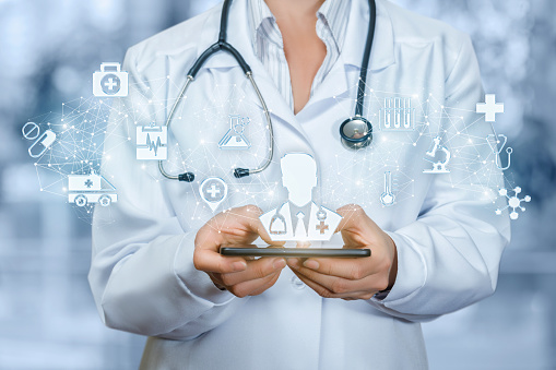 istock Doctor holding phone with male doctor on the screen. 1032149232