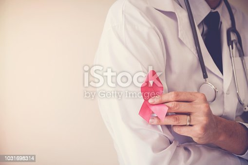 istock Doctor holding pink ribbon, breast cancer awareness, October pink concept 1031698314