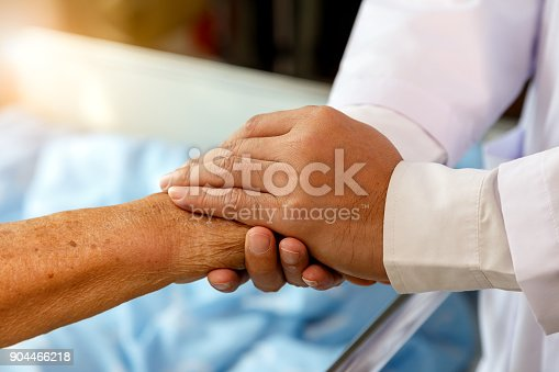 istock Doctor holding senior patient's hands in bed at hospital room, health care and people concept 904466218