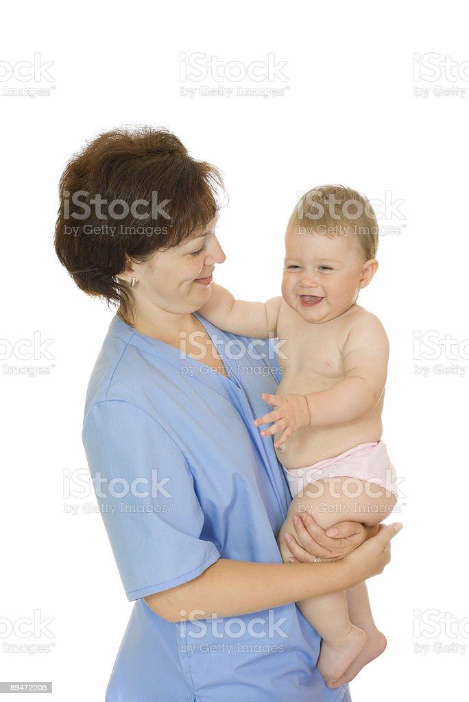Médico y bebé sonriente sosteniendo aislado pequeño foto de stock libre de derechos