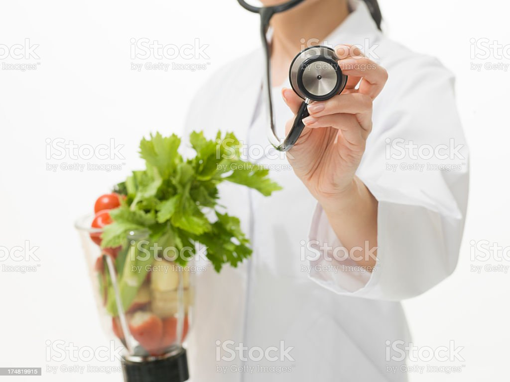 Doctor holding stethoscope and Vegetable juicer royalty-free stock photo