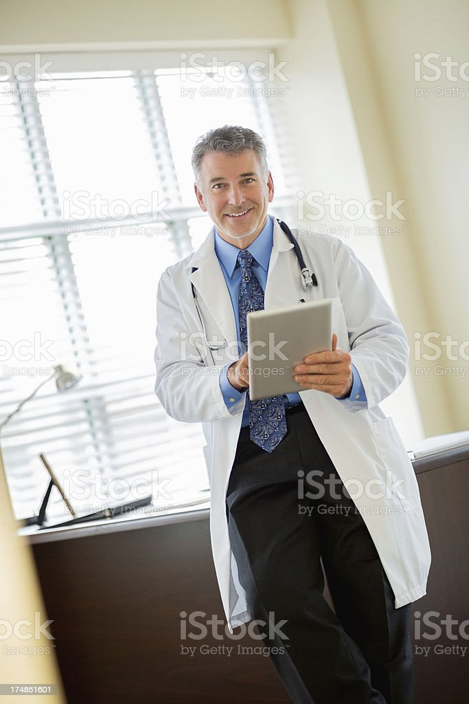 Doctor Holding Tablet Computer While Leaning On Desk royalty-free stock photo