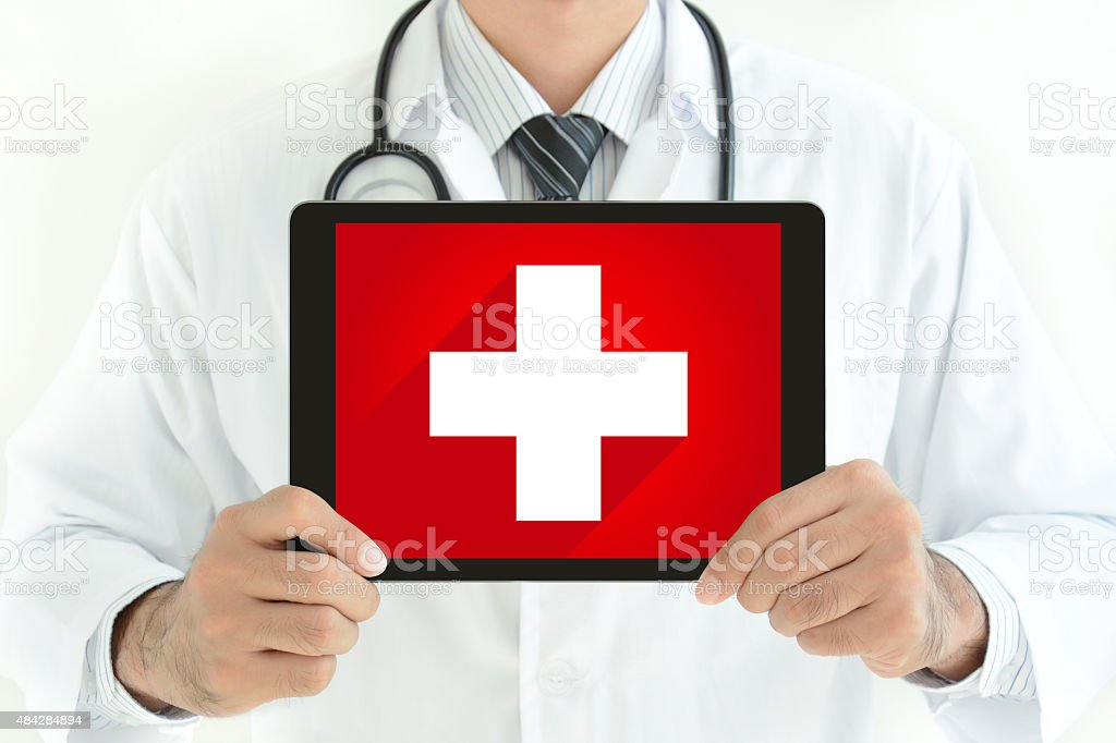 Doctor holding tablet pc with first aid sign on screen stock photo
