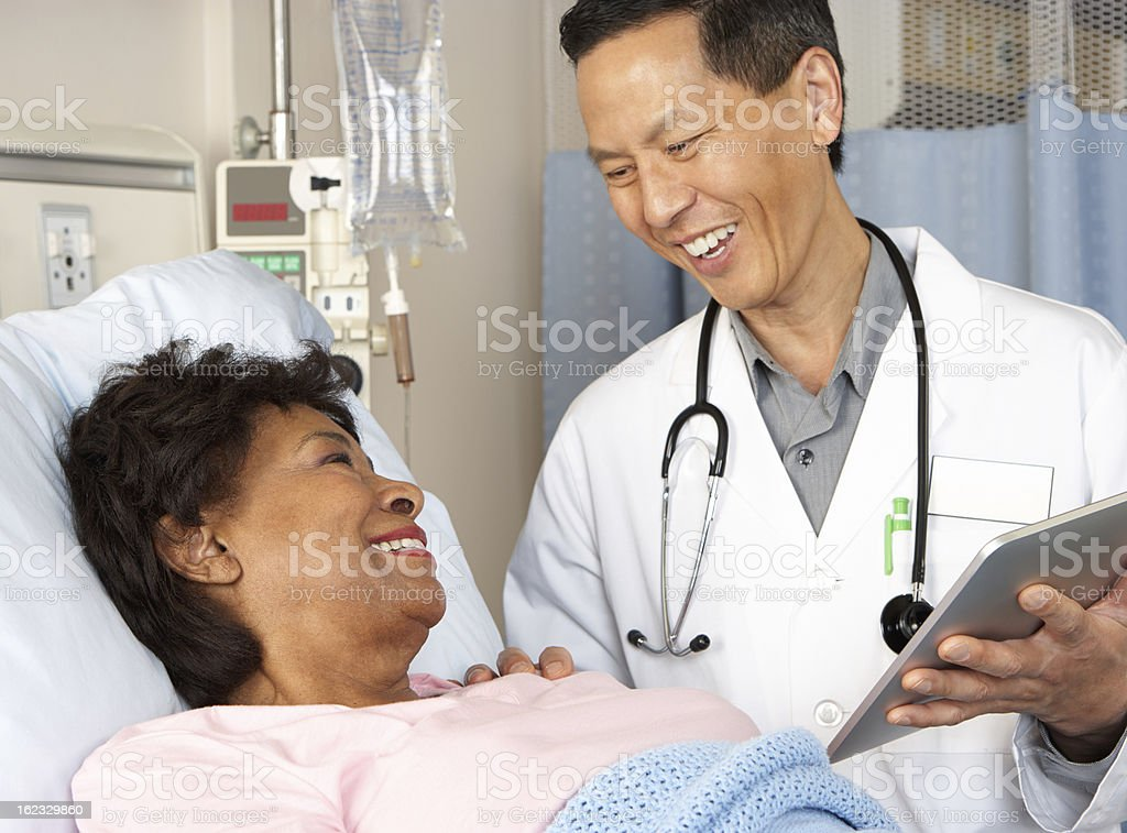 Doctor holding tablet talks with smiling patient stock photo