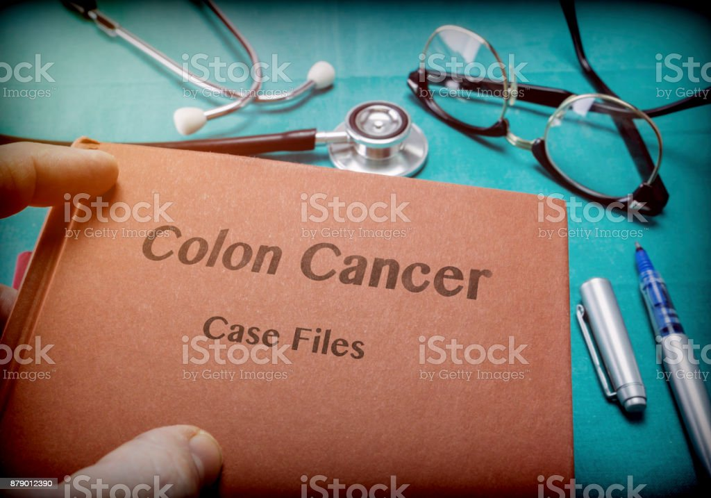 Doctor Holds Book On colon cancer In A Hospital stock photo