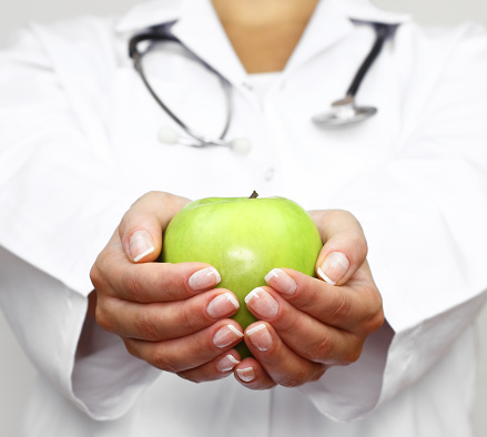 Doctor holds green apple