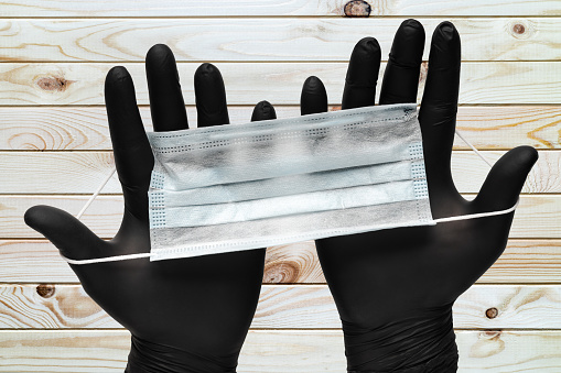 Doctor holds surgical face masks in two hands in black medical gloves on wooden plank brown background. Concept pandemic outbreak, virus prevention. Close-up view.