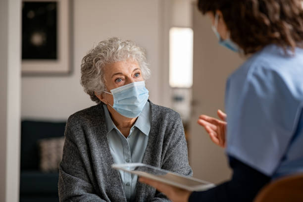 Doctor home visit a senior woman during the covid-19 pandemic stock photo