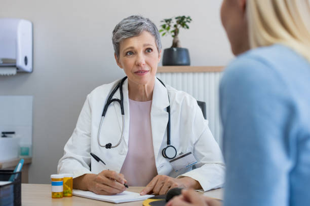 Doctor in a consultation Senior female doctor listening to patient explaining her painful in her office. Mature woman doctor consulting patient in hospital room. Doctor and patient discussing health issue in office. general practitioner stock pictures, royalty-free photos & images