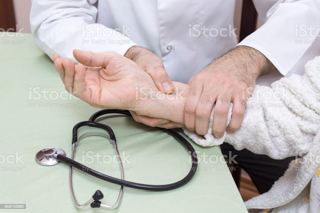 A doctor in a white coat examines the pulse on the wrist of an old woman in a white bathrobe. The stethoscope is on the table stock photo