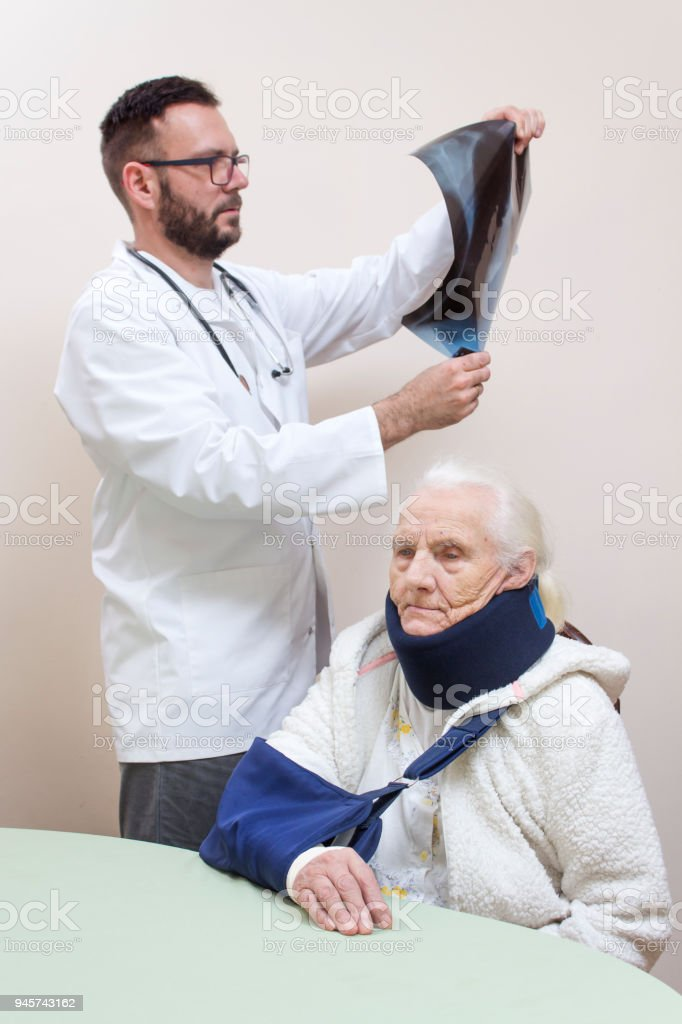 A doctor in a white coat is watching an X-ray picture. An old gray-haired woman is sitting on a chair with a sling on her arm and an orthopedic collar on her neck. stock photo