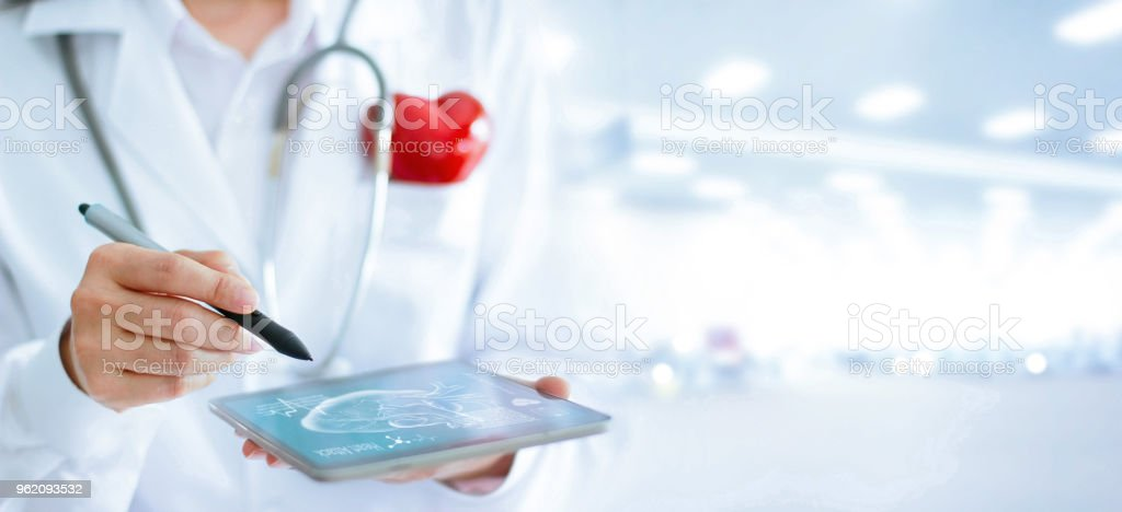 Doctor in cardiologist with stethoscope and red heart shape using tablet to analyze, diagnose for healthcare treatment stock photo