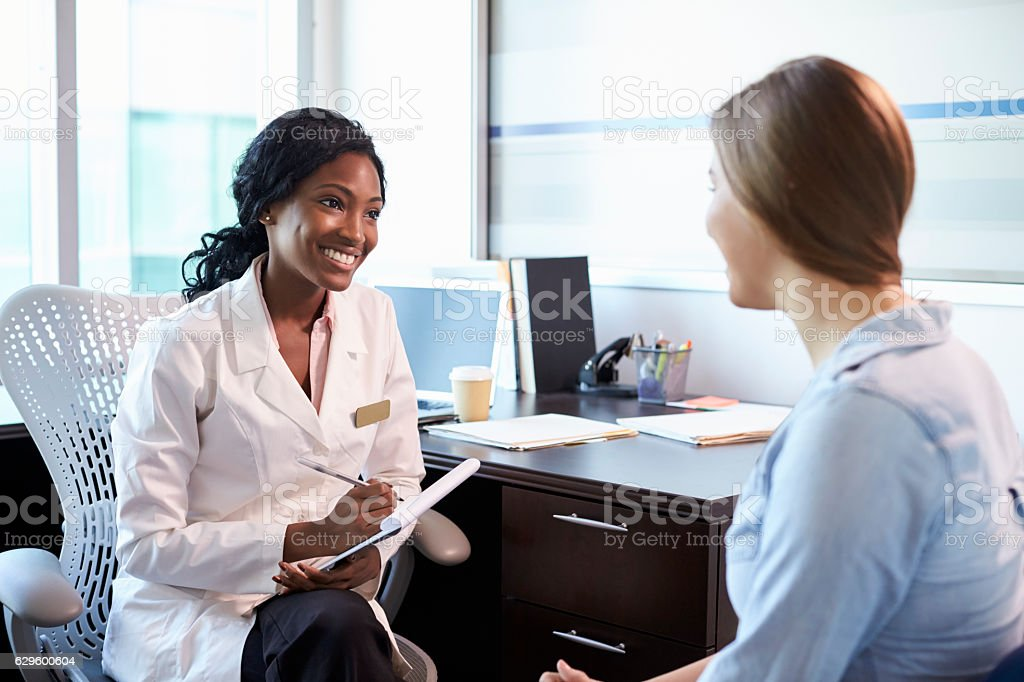 Doctor In Consultation With Female Patient In Office stock photo
