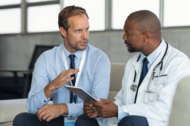 doctor in conversation with pharmaceutical representative - sales foto e immagini stock