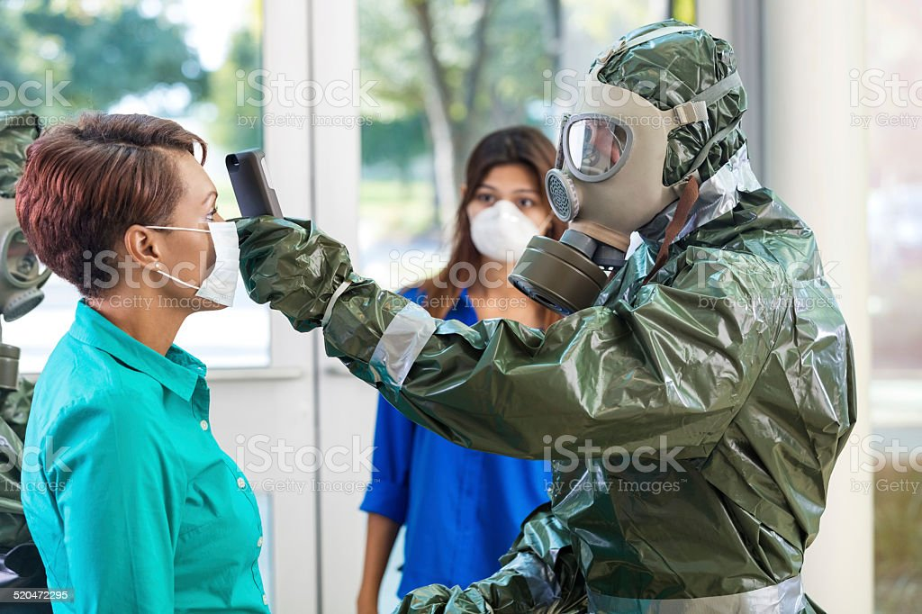 Doctor in hazmat suit examining woman during contagious outbreak stock photo