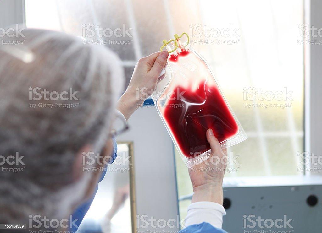Doutor em traje para operações está verificando um saco de sangue - foto de acervo