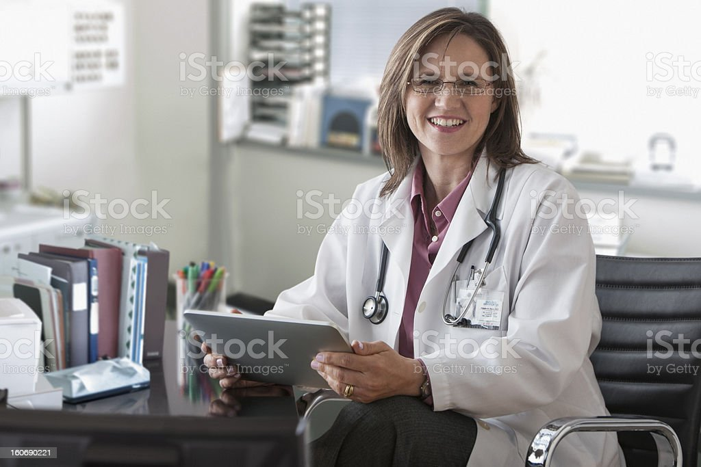 Doctor in her office smiling royalty-free stock photo
