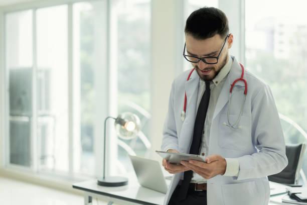 Arzt im Krankenhaus arbeiten mit moderner Technik für gesunde. Freundlicher Mann Arzt suchen und Lächeln für gutes Ergebnis von Patientendaten Diagramm. – Foto