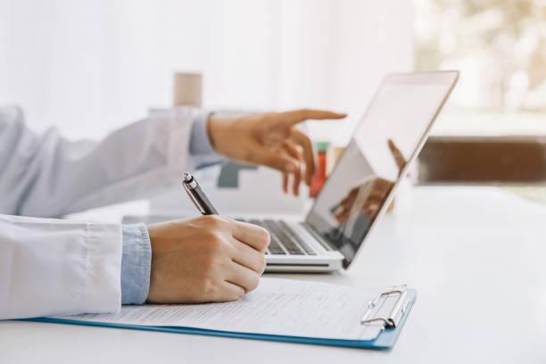 병원에서 의료 문서를 작성하고 노트북을 사용하는 의사 - 의사 뉴스 사진 이미지