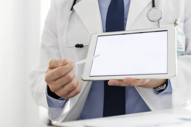 doctor in labcoat showing digital tablet at hospital - объяснять стоковые фото и изображения
