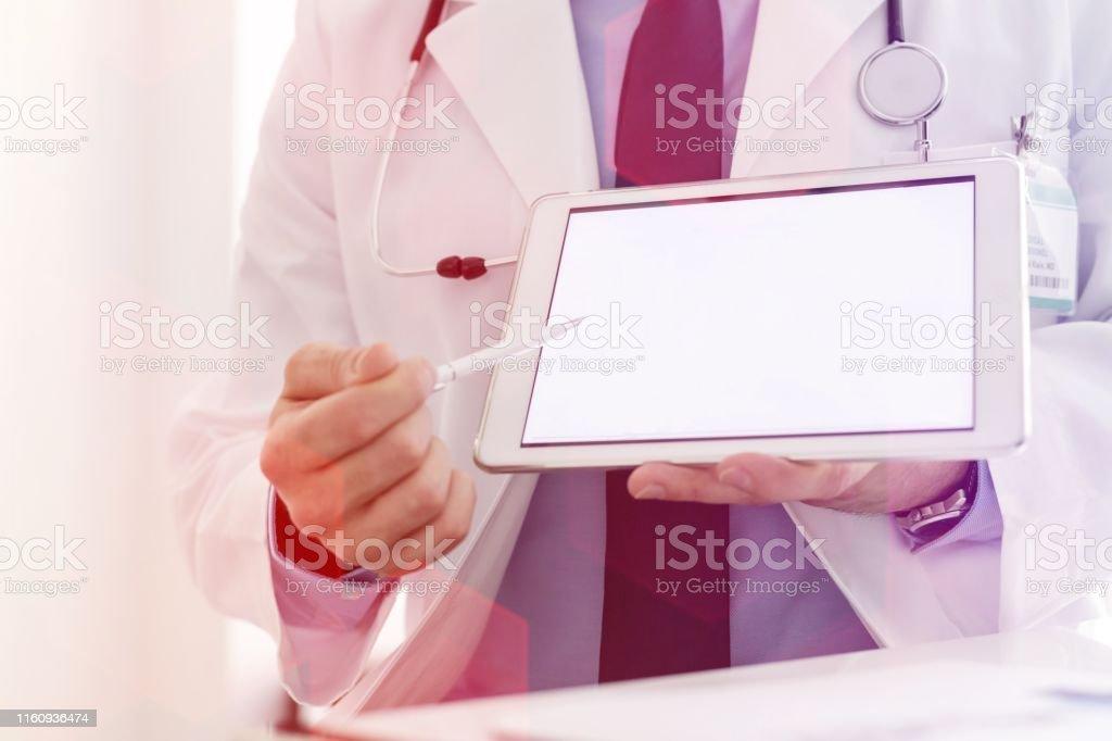 Doctor in labcoat showing digital tablet at hospital