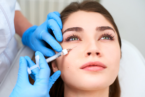 Beautician doctor in medical gloves with syringe injects botulinum under eyes for rejuvenating wrinkle treatment. Filler injection for under eye wrinkles smoothing. Plastic aesthetic facial surgery in beauty clinic