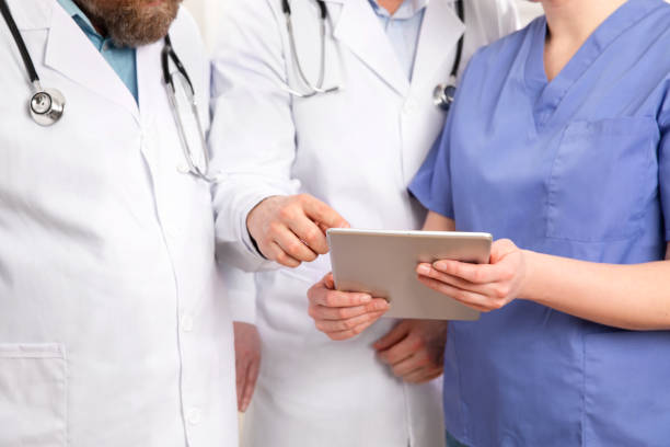 Doctor in medical team discussing patient report at tablet computer in hospital stock photo