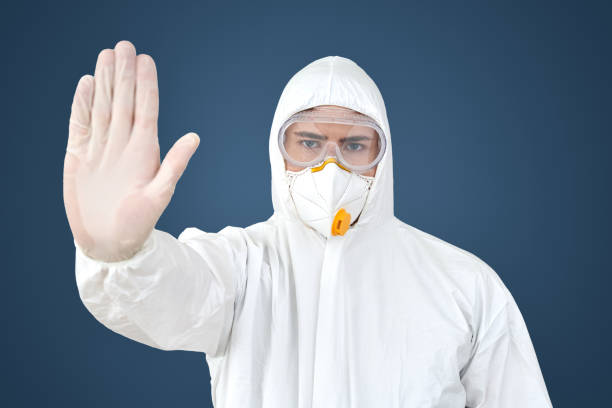 Doctor in protective suit and face mask making stop gesture stock photo