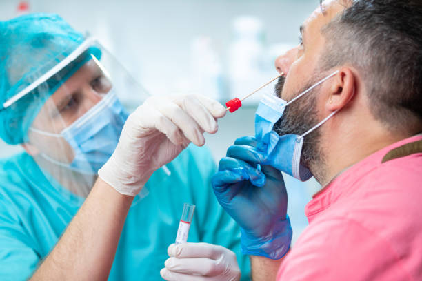 Doctor in protective workwear taking nose culture swab from patient stock photo