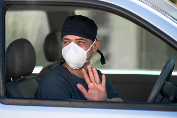 Doctor in scrubs and face mask driving outdoors in vehicle side view waving goodbye stock photo