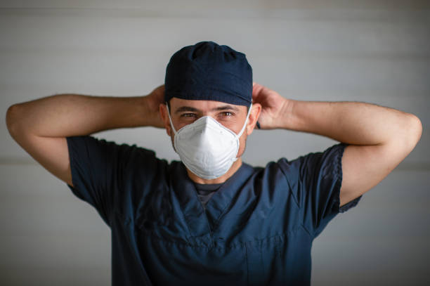 Doctor in scrubs and face mask portrait during lockdown fastening mask looking at camera stock photo