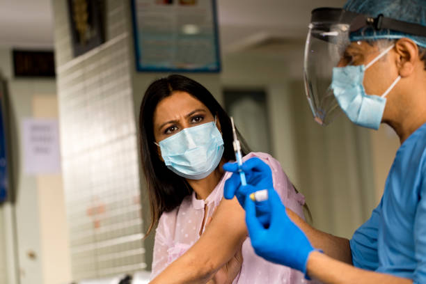 Doctor in surgical gloves pulling vaccine liquid from vial to vaccinate female patient stock photo