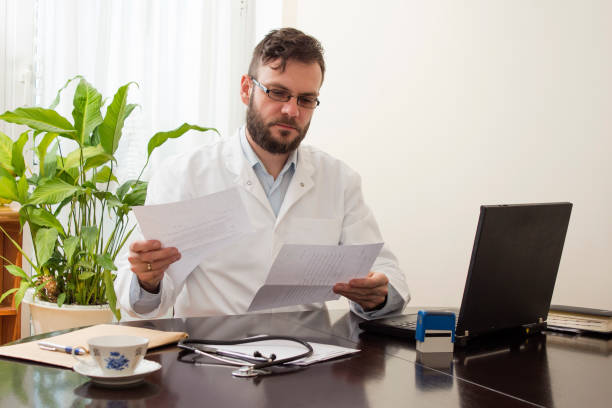 Doctor in the office sitting at a desk and reading medical records stock photo