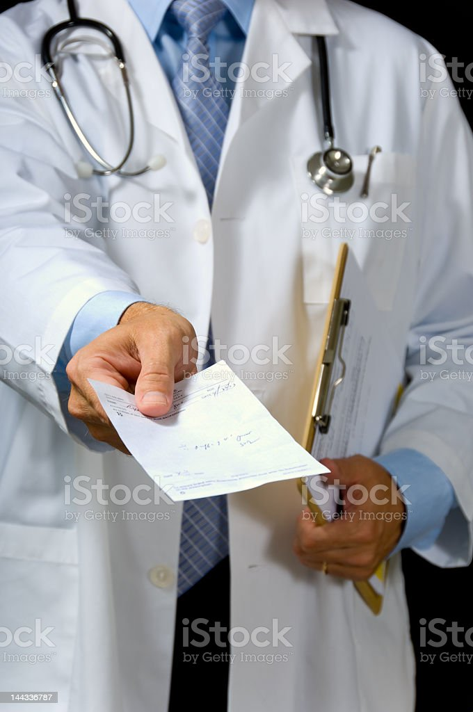 Doctor in white coat handing out prescription stock photo
