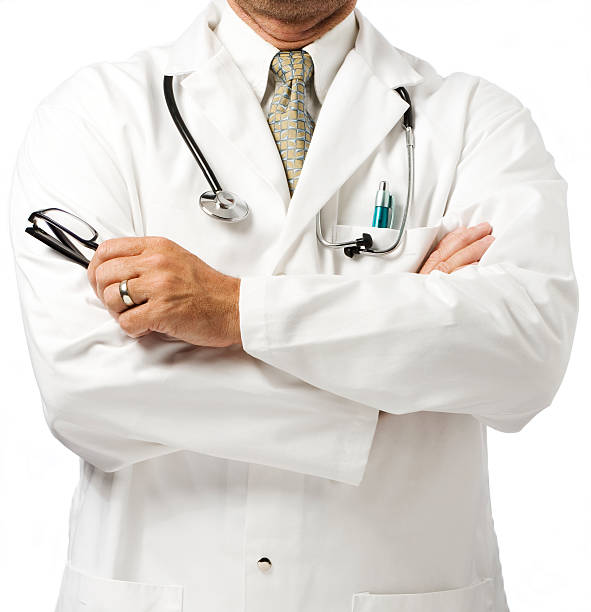 Doctor in white coat with folded arms stock photo