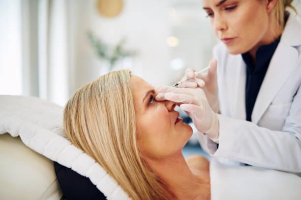 arzt botox injektion in eine reife frau stirn - peeling herstellen stock-fotos und bilder