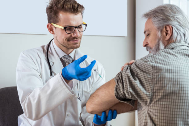 Doctor injecting senior patient Doctor injecting senior patient in clinic. Medical exam. Vaccination.. only mature men stock pictures, royalty-free photos & images
